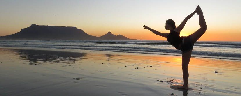 Shows a woman doing Sunset Yoga on the beach