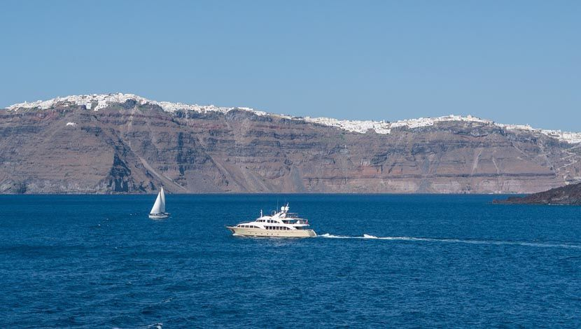 Shows a yacht sailing by and island