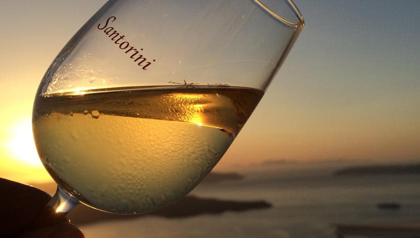 Shows a wine tasting session with a view in Santorini
