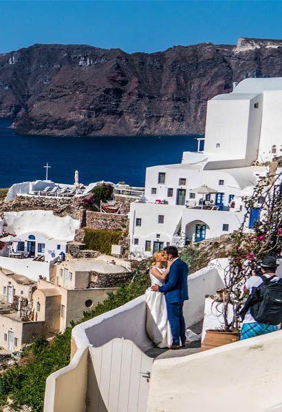 Shows a couple kissing in Oia, Santorini