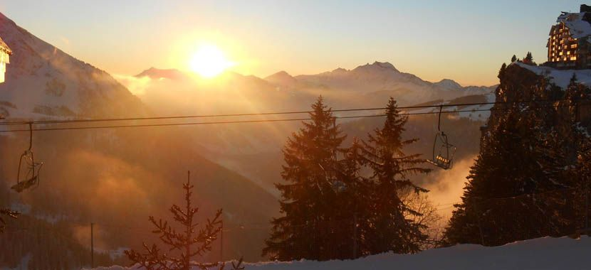 Tips for a France skiing holiday - Shows sunset over a snowy mountain