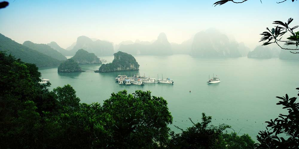 The Ha-long Bay cruise - Shows a misty view of Halong Bay with boat in the distance