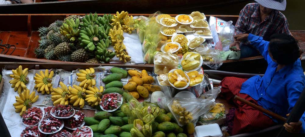 Tips for eating and drinking in Thailand - Shows a river market seller