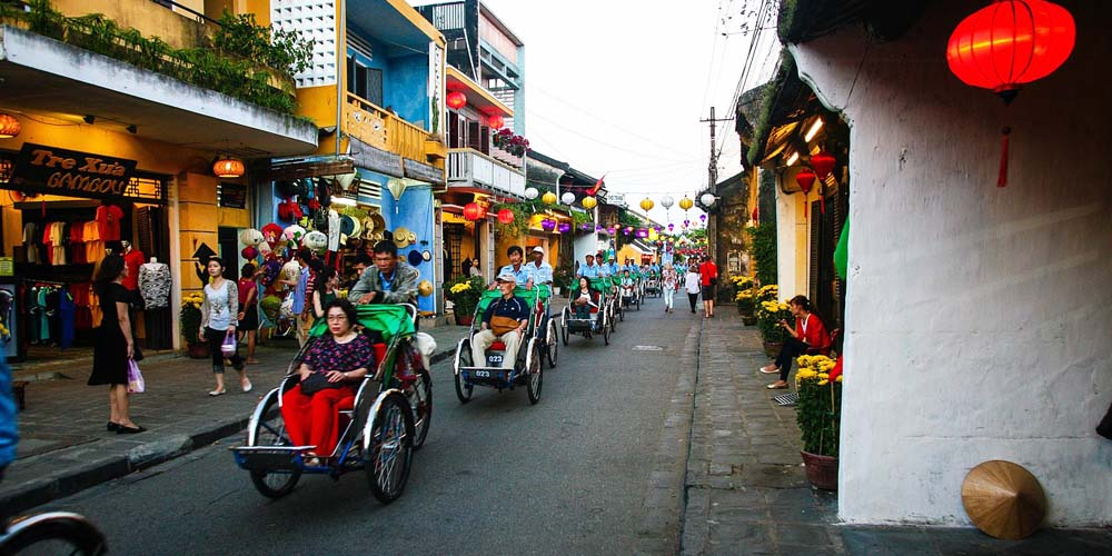 Shows a group of Tuk Tuk's driving through Hoi An