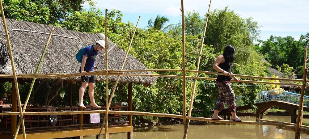 Vietnam travel tips - Shows a couple crossing a bamboo bridge