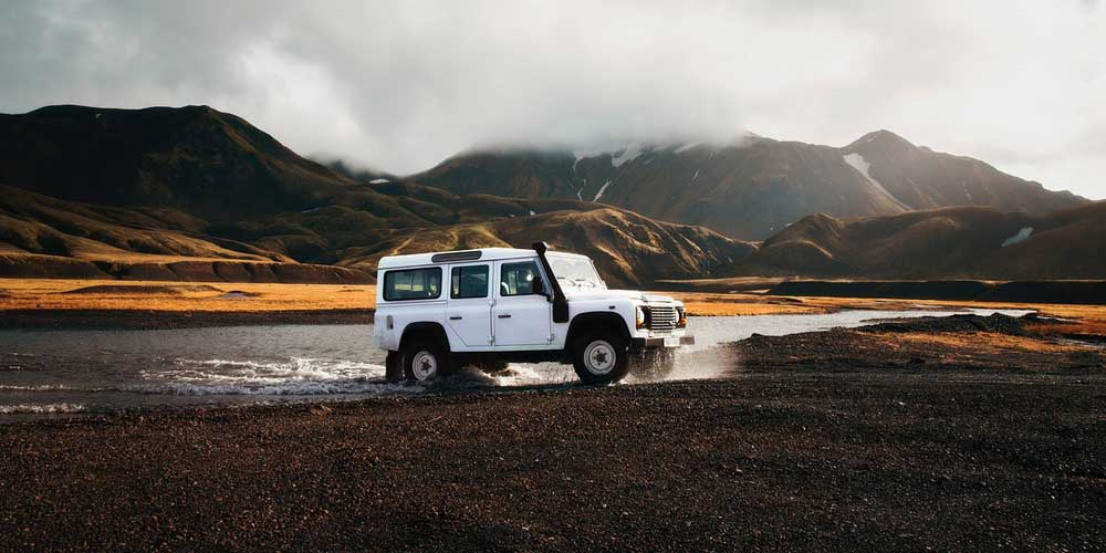 Iceland car hire tips - Shows a 4x4 car driving over rough terrain