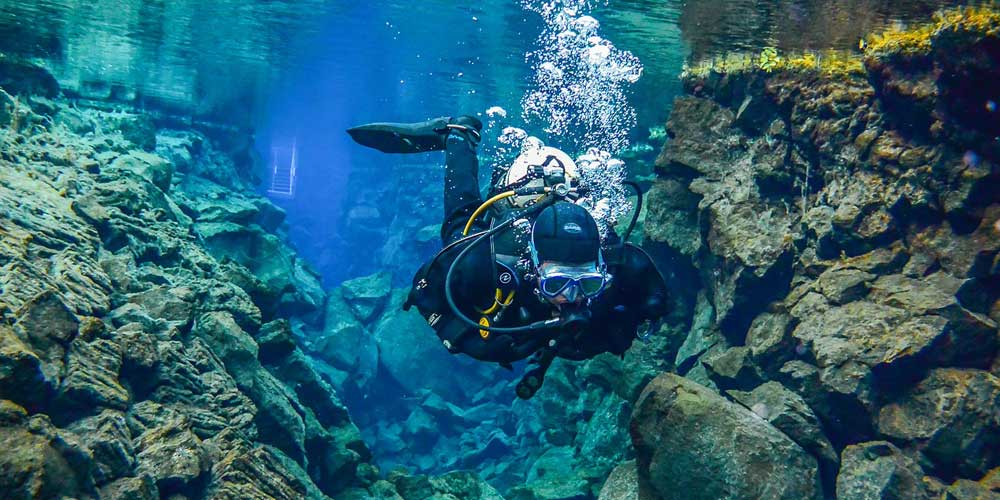 Shows a person scuba diving at Silfra