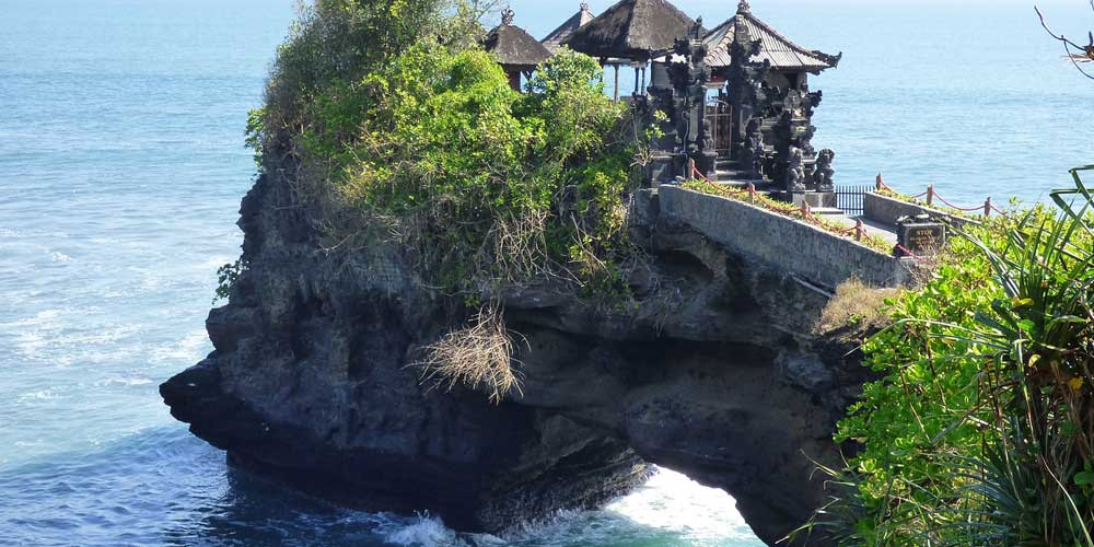 Shows an iconic Balinese temple on a rock stack - Where to stay in Bali