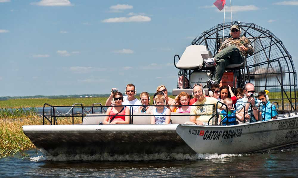 Boggy Creek air-boat rides - depicts an air-boat with people enjoying a ride.