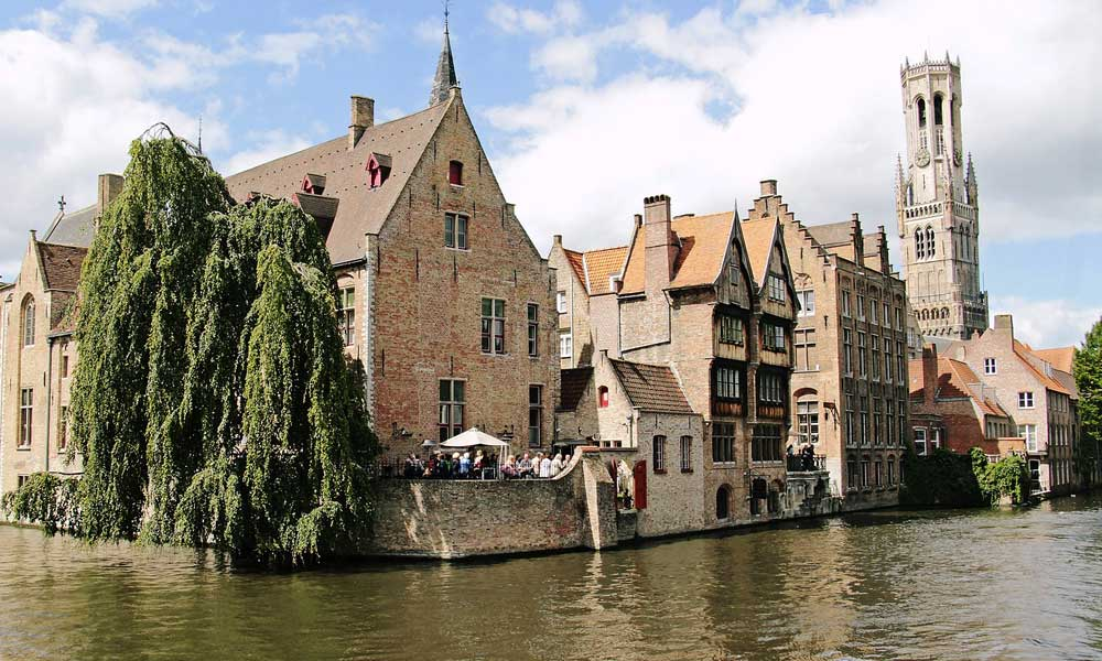 April city break ideas - depicts the river and quaint buildings of Bruges, Belgium