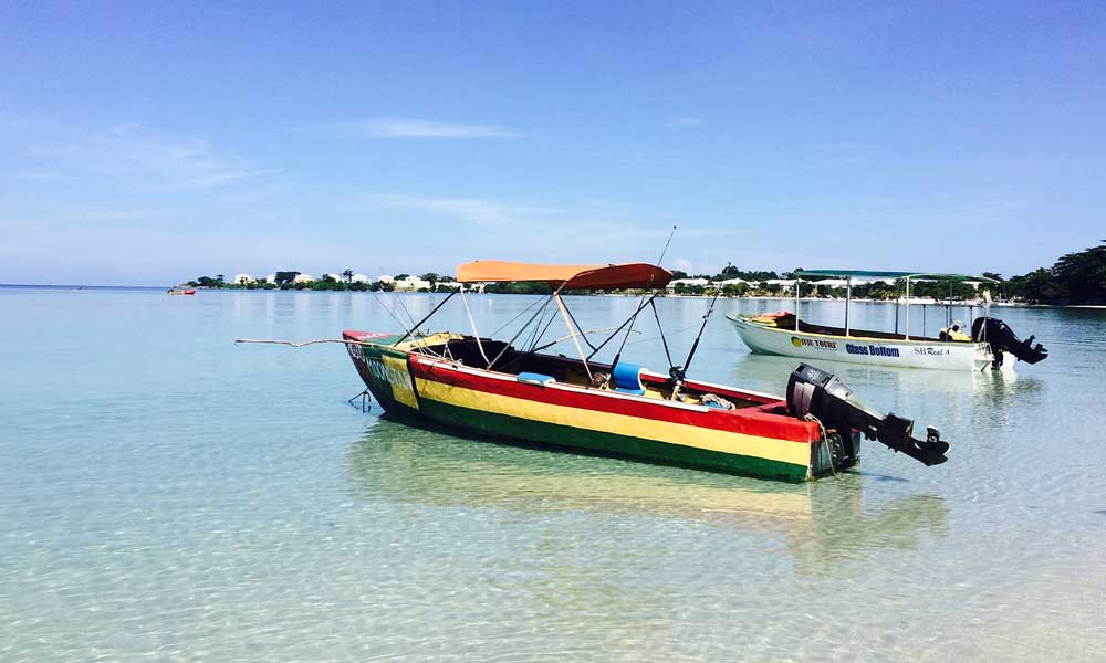 April holiday sun - Depicts Jamaica shore with colourful boats