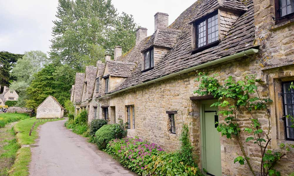 Depicts quaint village in the Cotswolds - Best places to visit in the UK outside of London