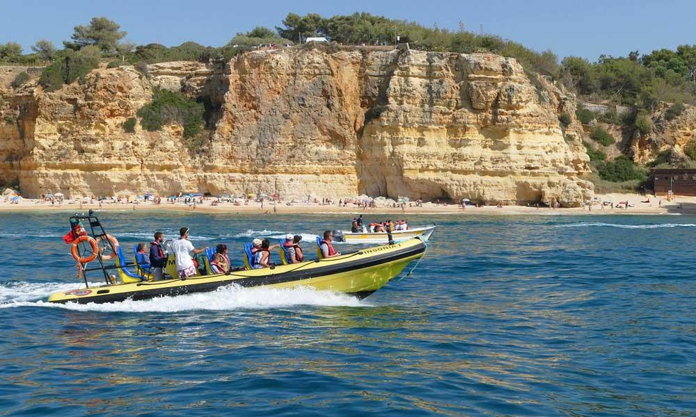 Depicts Algarve tourist boat alongside the beach - Albufeira Travel Guide
