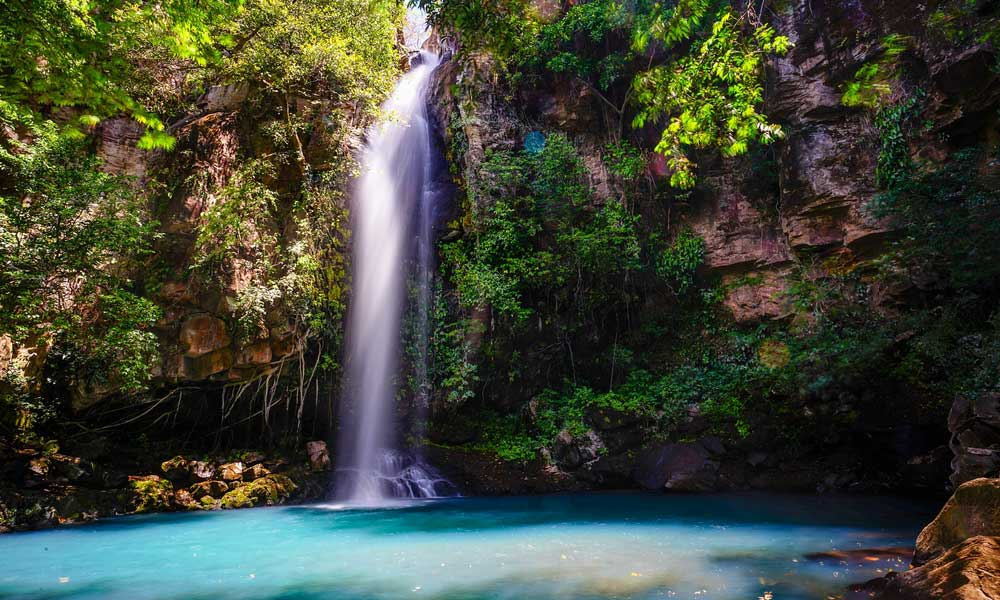 Depicts turquoise waterfall in Costa Rica - adventure holiday ideas