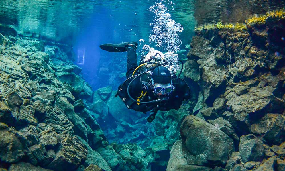 Adventure holiday ideas - Depicts scuba diver in Iceland