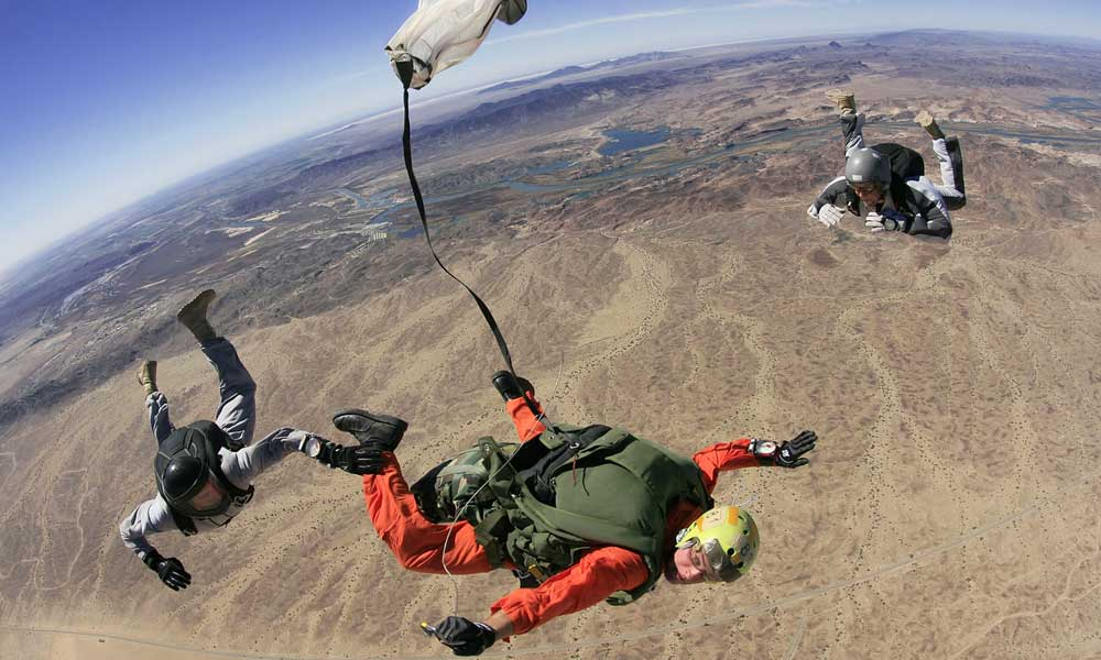 Depicts a trio skydiving above South Africa dessert - South Africa adventure