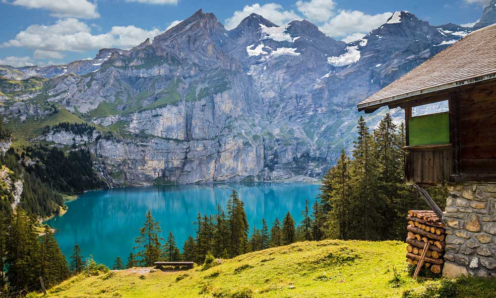 Depicts cabin overlooking a lake beneath mountains in Switzerland
