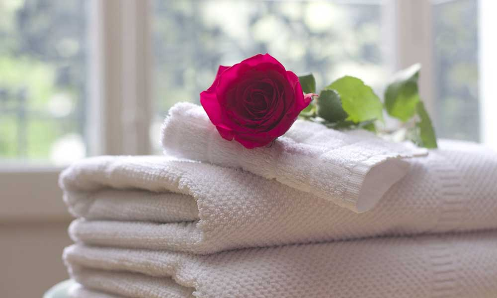 Holiday hacks and tips - Hotel amenities and perks - Depicts stack of hotel towels