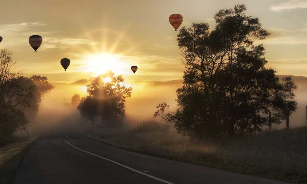 Tips for taking good travel photographs - Depicts hot air balloons at sunset