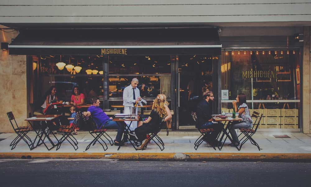 Holiday tips - always check restaurant reviews. Depicts people dining outside
