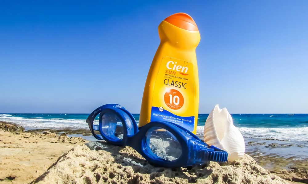 Depicts sun lotion on a beach - holiday accessories tips