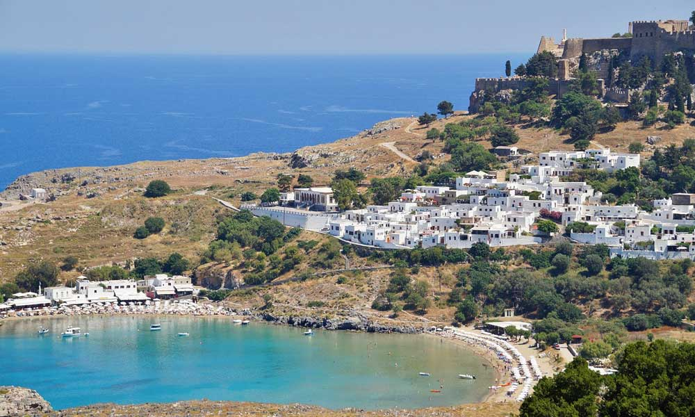 October half term holiday ideas - Shows Lindos town beach in Rhodes