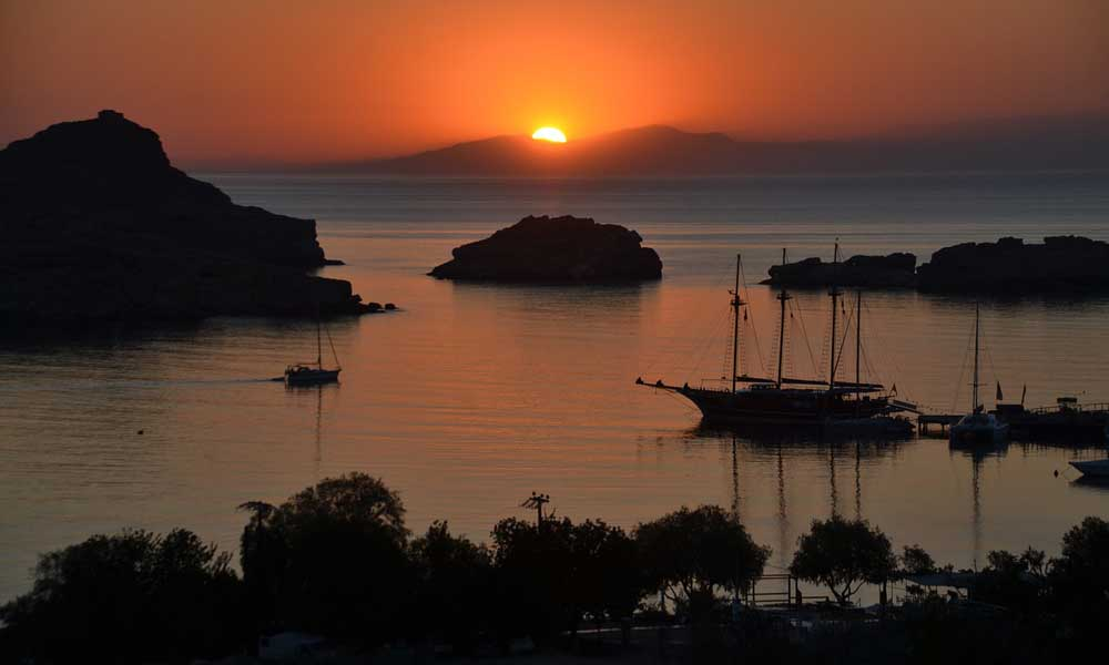 Lindos travel guide tips - shows the sunset by Lindos bay