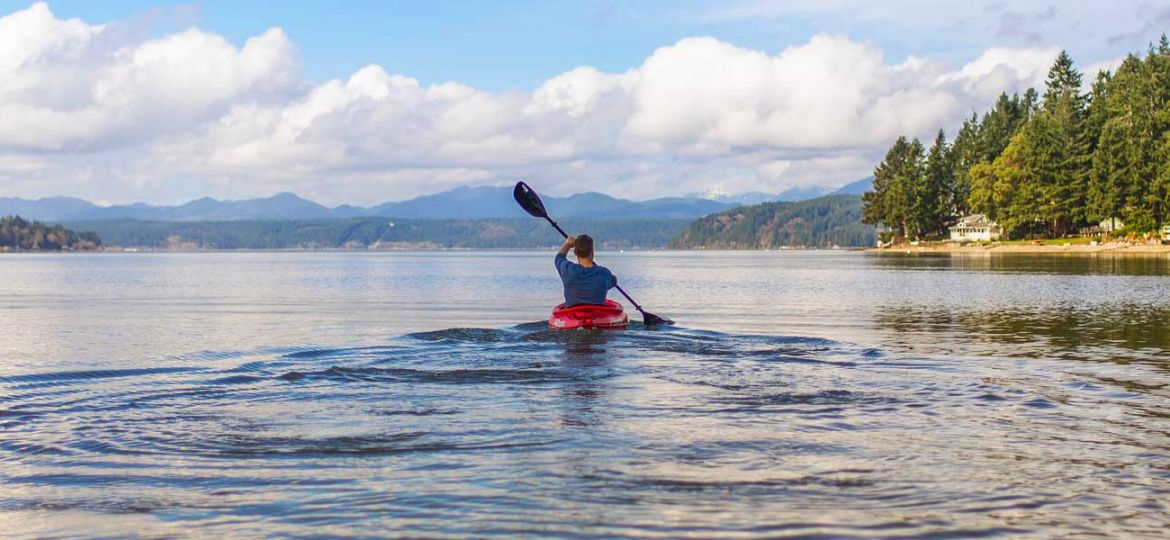 10 epic adventure holiday ideas - depicts man in kayak on lake