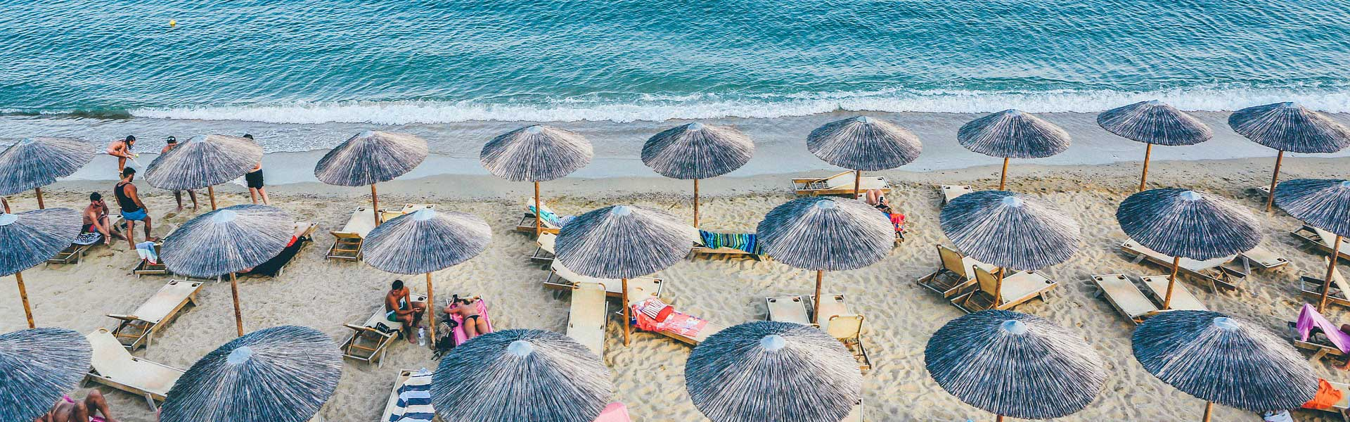 28 Holiday tips, tricks and hacks - Top banner depicting beach umbrellas