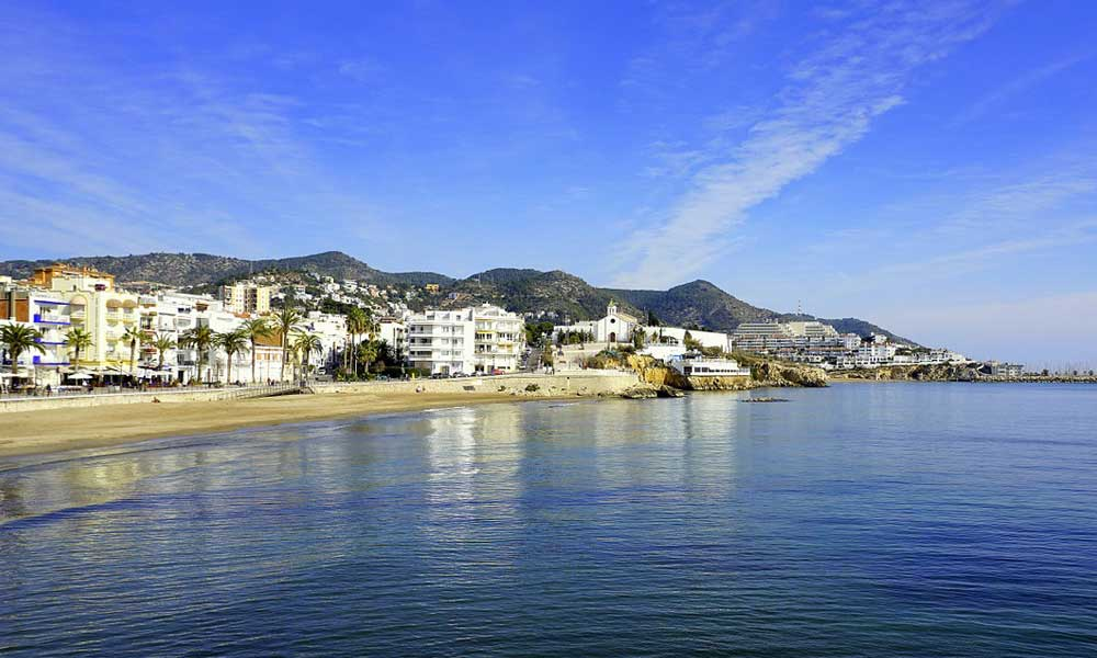 Shows the quaint town of Sitges in Spain - July beach holiday ideas