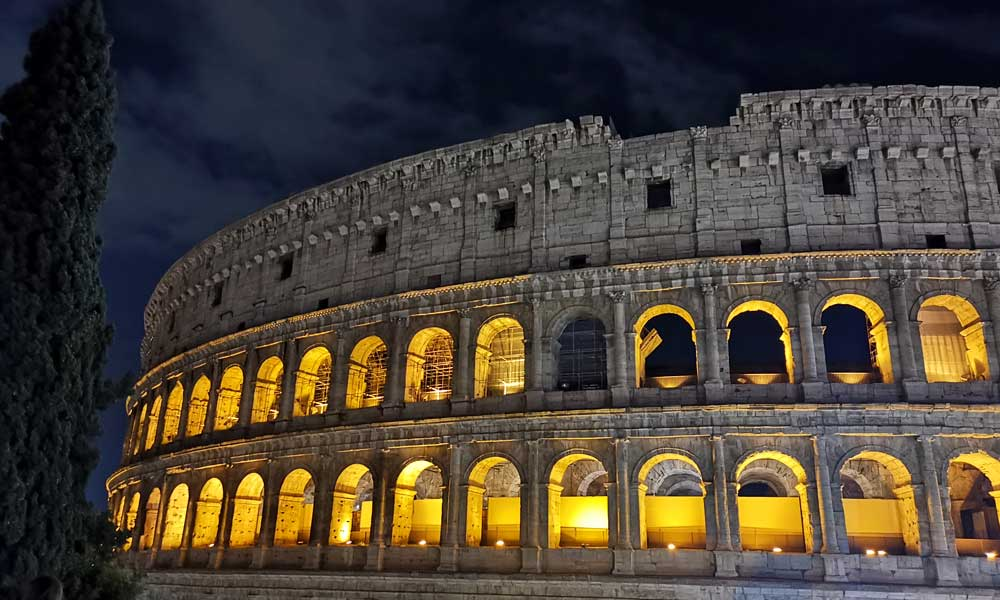 Shows the Roman Colosseum at night - Best area for nightlife in Rome