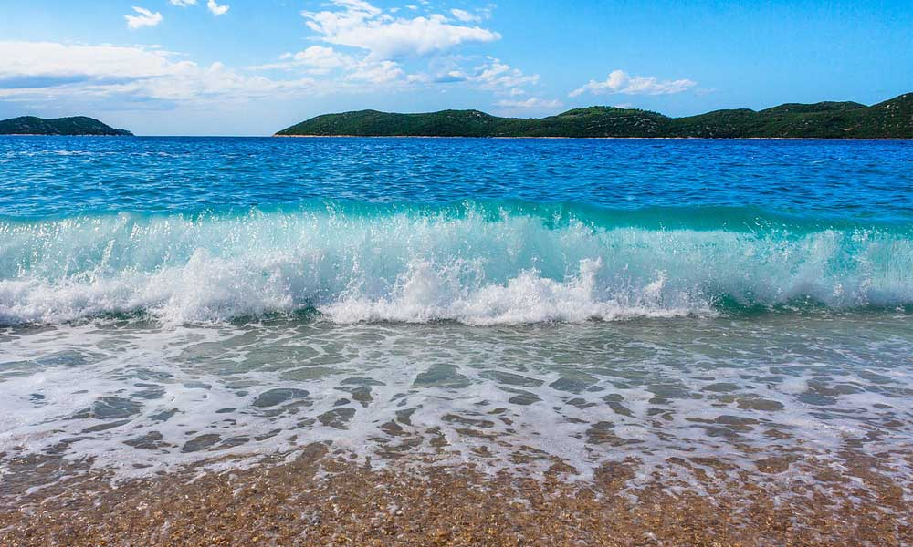 Shows beautiful Croatian beach with waves crashing against the pebbles - Best Zadar beaches