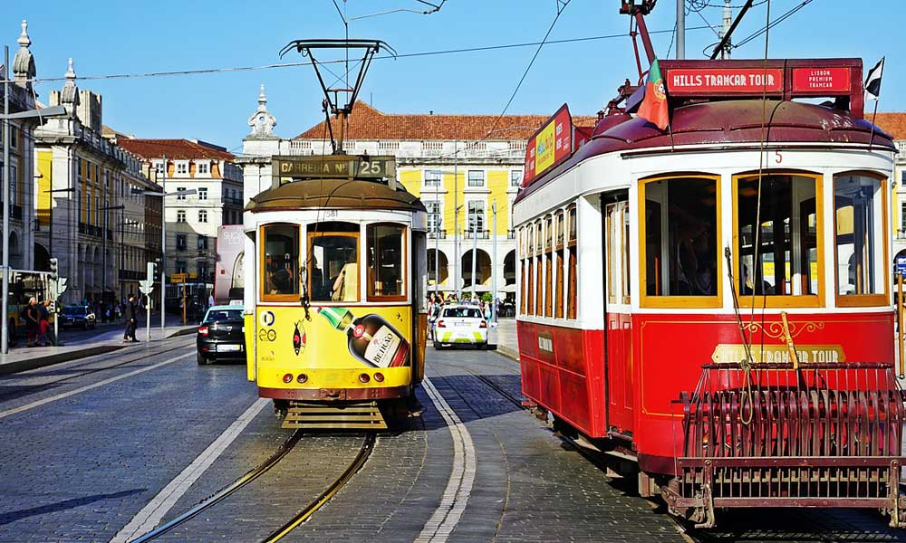 Lisbon travel tips - Shows two trams on the streets of Lisbon
