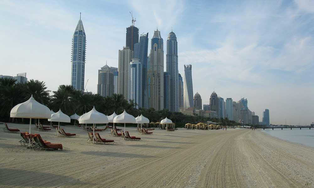 Show Dubai beach and city skyscrapers - October half term beach holidays