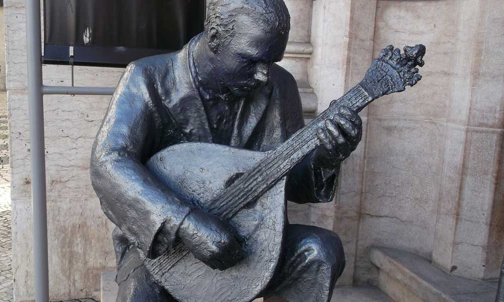 What to do in Lisbon - shows a statue playing traditional Fado music
