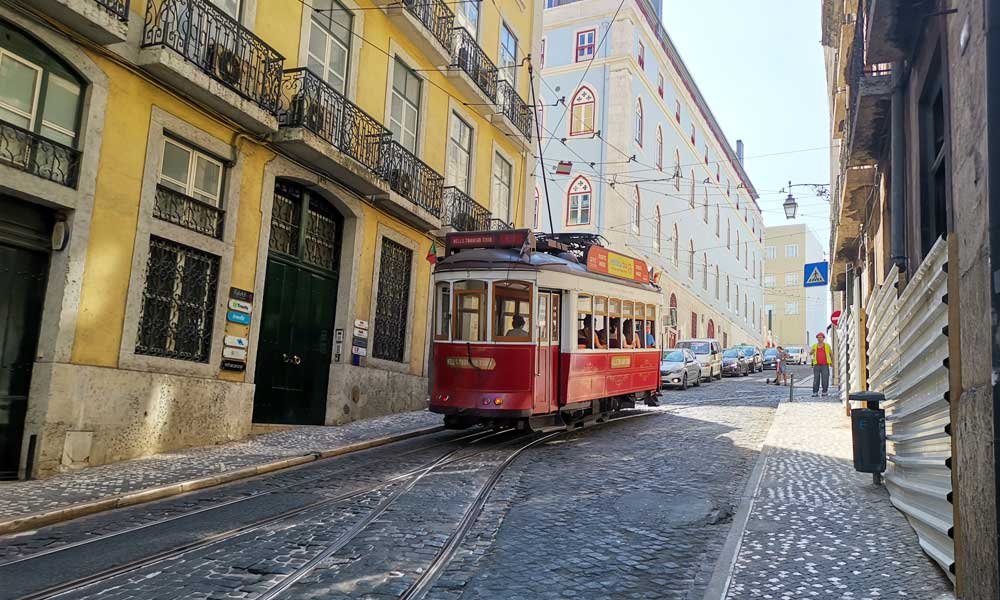 Shows a tram on the streets of Lisbon - Portugal road trip ideas