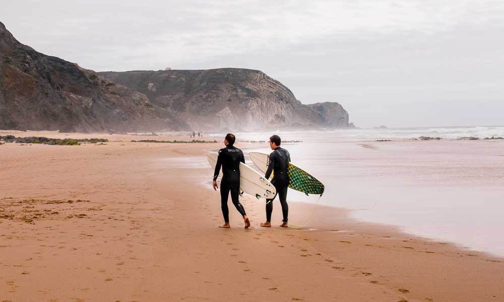 Top tips for a Portugal road trip - shows two surfers on a beach