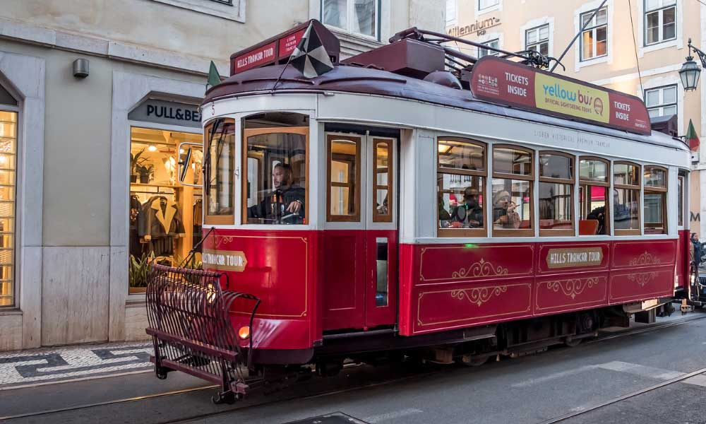 How to get from Lisbon to Porto and Porto to Lisbon - shows a red tram in Lisbon