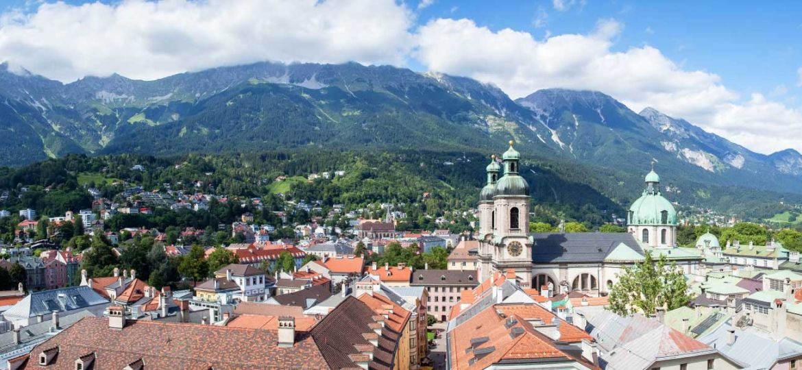 Where to go on holiday in November - shows the mountains and town on Innsbruck, Austria