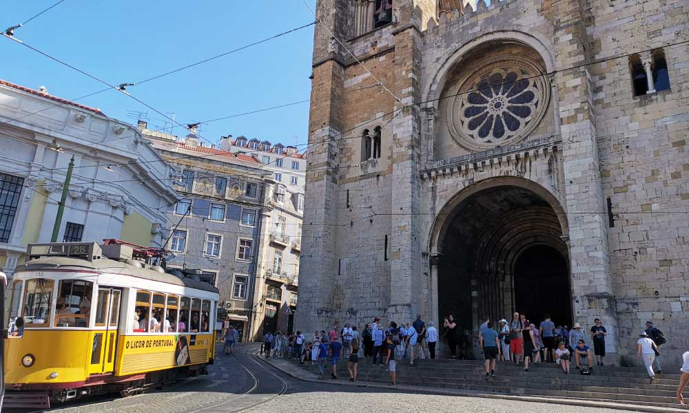 Top tips for finding the best place to stay in Lisbon - Shows yellow tram and church