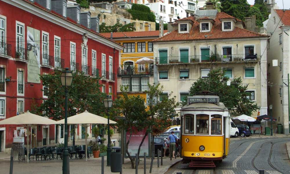 Best places to stay in Lisbon - Shows the streets of Graca with a yellow tram