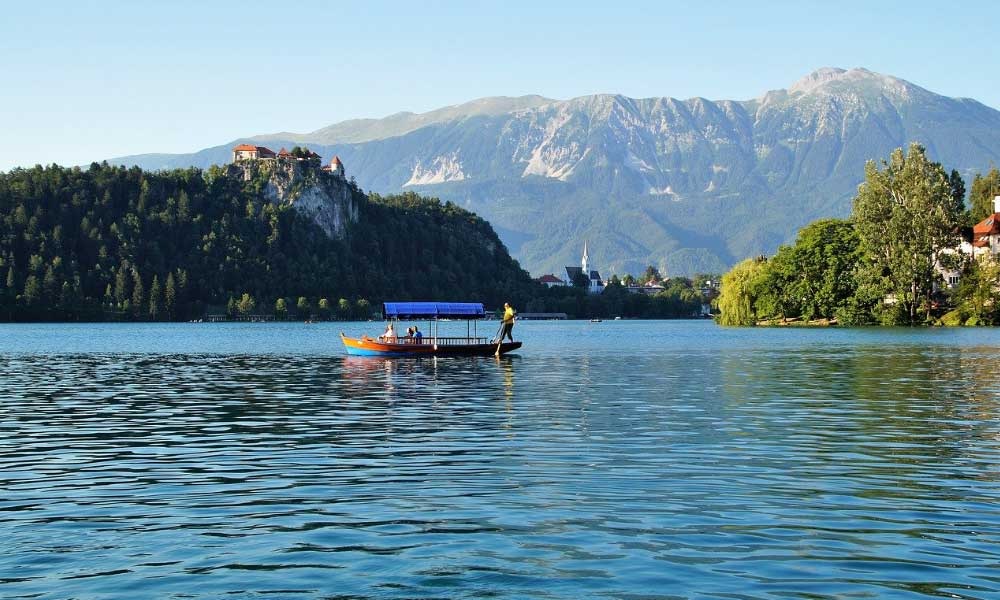 Shows a boat sailing on Lake Bled during the summer
