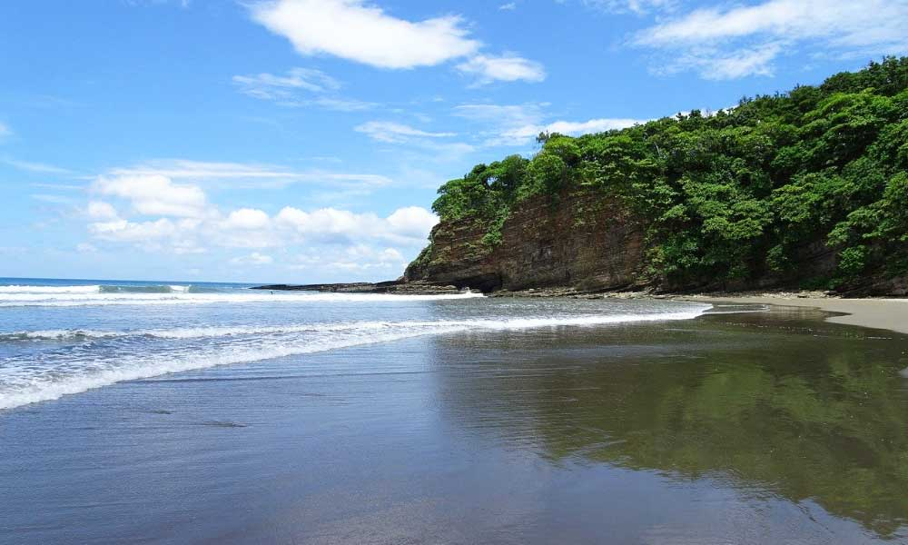 Cheap countries to go on holiday in Central America - Shows a beach in Nicaragua surrounded by trees