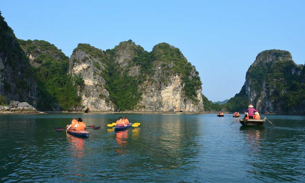 Cheapest countries to visit in South East Asia - Shows a group kayaking at Halong Bay