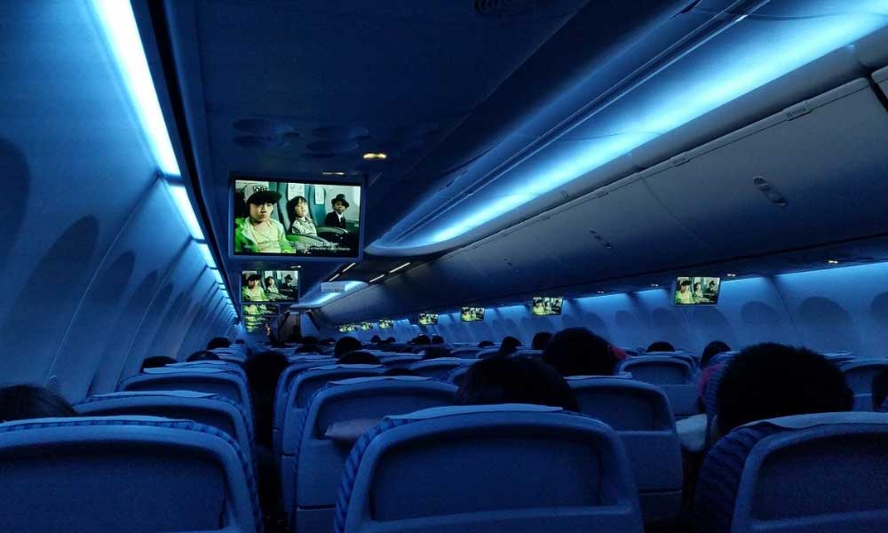 Shows an airplane cabin playing movies - Things to do on a long distance flight