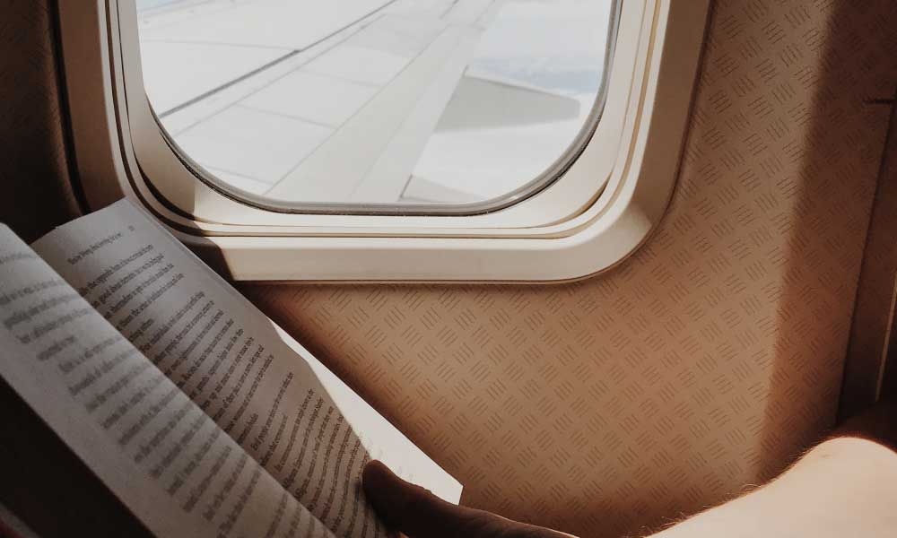 Shows a man reading a book on a plane - Activities for a long haul flight