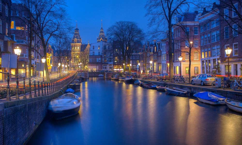 Shows the canals of Amsterdam at night