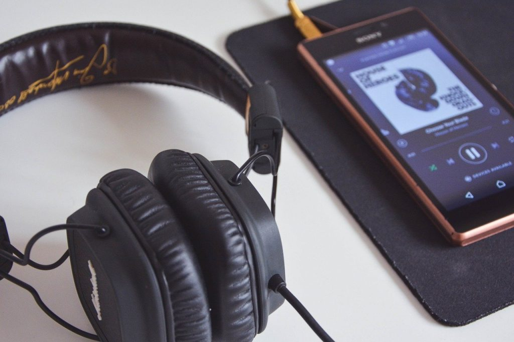 Depicts a set of headphones and phone playing Spotify music - In-flight activities