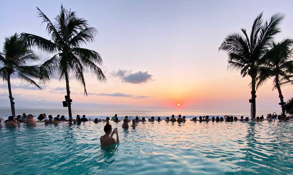 Shows a hotel swimming pool at sunset in Seminyak