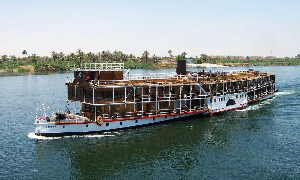 Shows a cruise boat sailing down the river Nile